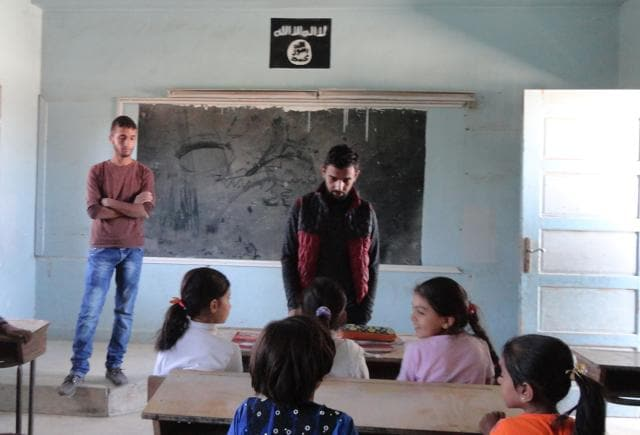 Syrian children sit at a classroom adorned with an Islamic State group insignia on the first day of classes in the Syrian town of Manbij.