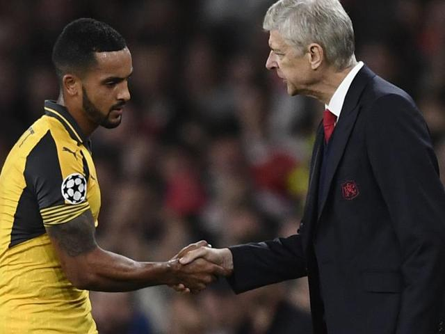 Arsenal's Theo Walcott shakes hands with manager Arsene Wenger as he is substituted.