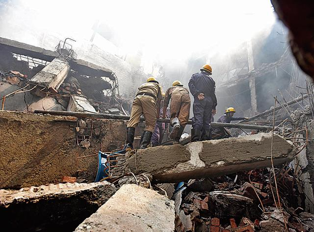 Firemen and people from other agencies dousing the fire at Narela Industrial Area in New Delhi on Thursday.