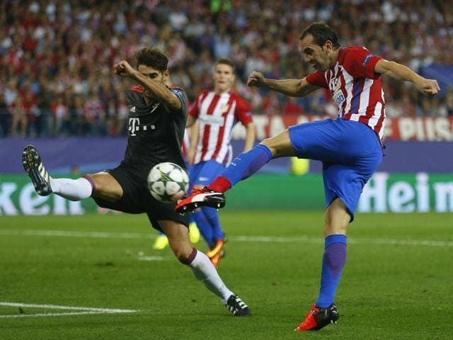 Atletico's Diego Godin, right, shoots the ball as Bayern's Javi Martinez tries to stop him.