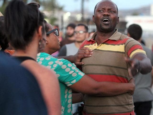 A man claiming to be Alfred Olango's cousin shouts at police during a rally in El Cajon, a suburb of San Diego, California on September 28, 2016, in response to the police shooting of Olango the night before. Protesters marched in a California town following the fatal police shooting of an unarmed black man said to be mentally ill, as local officials urged calm and pledged a full investigation. The victim, identified as Ugandan refugee Alfred Olango, 30, was shot on Tuesday in the San Diego suburb of El Cajon after police received an emergency call about a man behaving erratically and walking in traffic. / AFP PHOTO / Bill Wechter