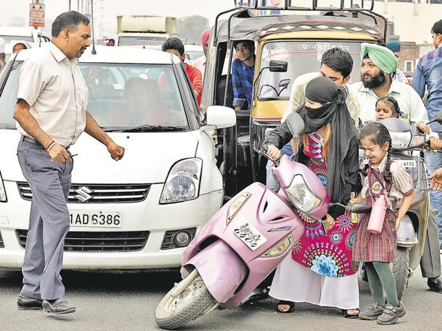 A woman stuck in the traffic chaos due to protest (right) by school vans and auto operators in Amritsar on Wednesday.