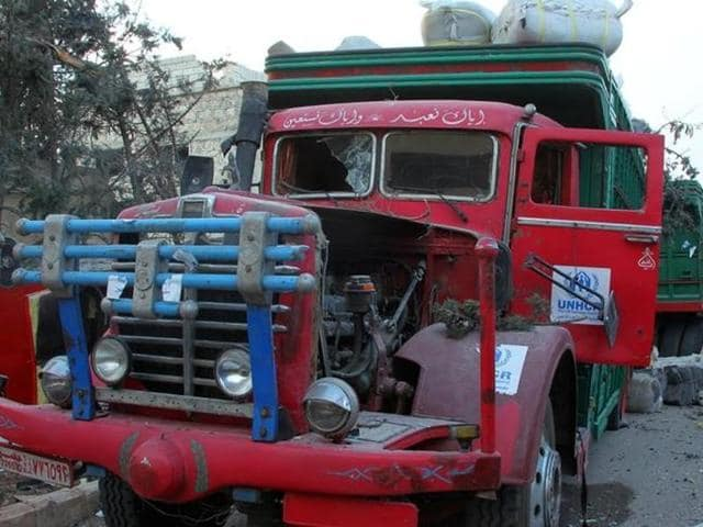This image provided by the Syrian anti-government group Aleppo 24 news, shows damaged trucks carrying aid, in Aleppo, Syria. .