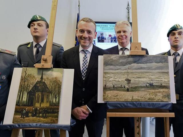 Director of Amsterdam's Van Gogh Museum Alex Rueger, center, stands next to the paintings Congregation Leaving The Reformed Church of Nuenen, left, and 1882 Seascape at Scheveningen by Vincent Van Gogh, during a press conference in Naples, Italy, Friday, Sept. 30, 2016.
