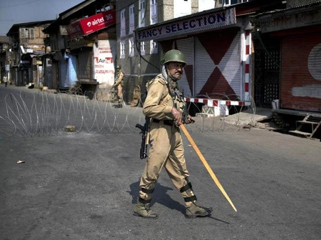 Paramilitary personnel stand guard during a curfew in Srinagar.