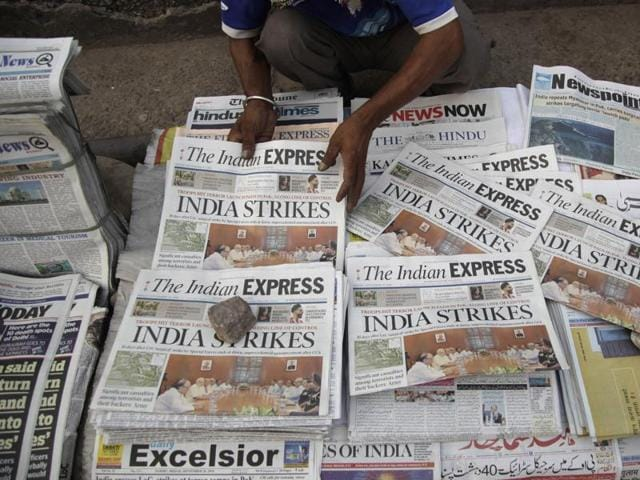 A newspaper vendor arranges morning newspapers carrying headlines of India's military strikes, in Jammu.