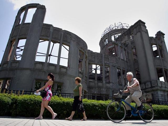 In this July 26, 2005 file photo, foreign tourists and a local cyclist go by the Atomic Bomb Dome at the Hiroshima Peace Memorial Park in Hiroshima. A bill passed by Congress allowing the families of 9/11 victims to sue the Saudi government has reinforced to some in the Arab world a long-held view that the US only demands justice for its own victims of terrorism, despite decades of controversial US interventions around the world.