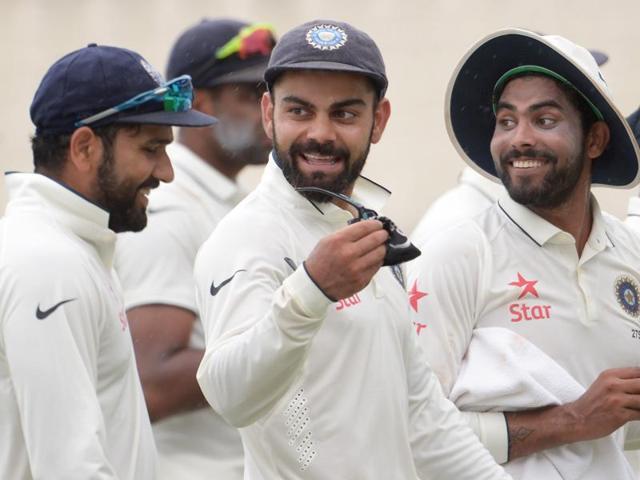 India's Bhuvneshwar Kumar (2R) with teammates celebrate the wicket of New Zealand's Martin Guptill.