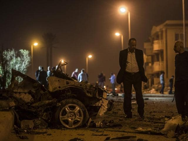Egyptian official inspect the wreckages of a car bomb exploded in a Cairo suburb after Egypt's deputy prosecutor general drove late on Friday.