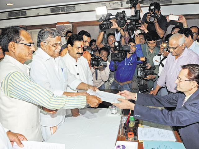 BJP leader La Ganesan (C) submits nomination papers for Rajya Sabha bypoll in Bhopal on Friday.
