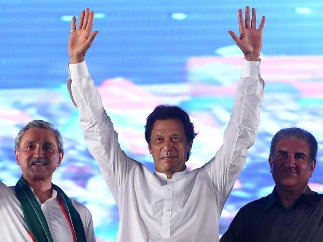 Pakistani cricketer-turned-opposition leader Imran Khan (C) waves to supporters during a public meeting in Raiwind on Friday night.