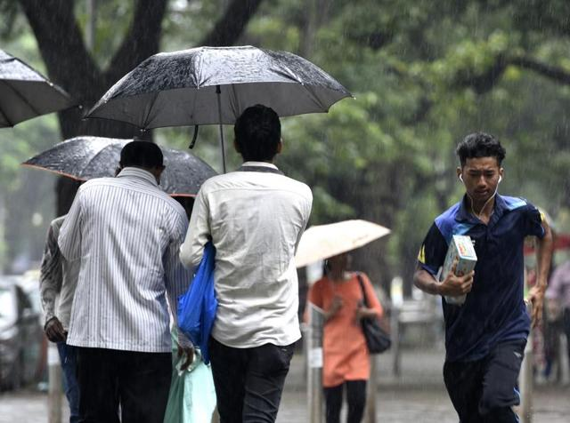 A man caught unaware during light rain in Mumbai, on Saturday