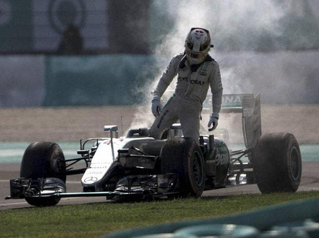 Mercedes driver Lewis Hamilton of Britain leaves his car after an engine failure during the Malaysian GP.