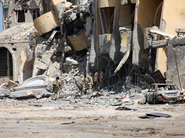 Libyan forces allied with the UN-backed government walk through a destroyed building during a battle with Islamic State fighters in Sirte.