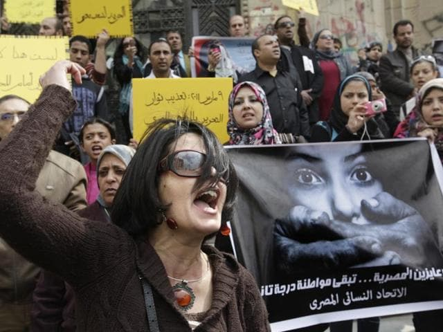 An Egyptian activist shouts anti-military Supreme Council slogans with a poster in Arabic reading