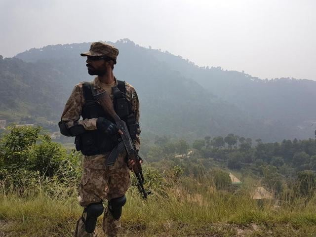 A Pakistani soldier patrols a village in district Bhimber near the Line of Control (LoC) in Pakistan-administered Kashmir during a media trip organised by the Pakistani army on October 1, 2016.