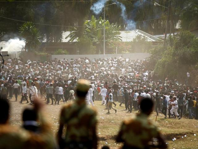Protestors run from tear gas launched by security personnel during the Irecha, the thanks giving festival of the Oromo people in Bishoftu town of Oromia region, Ethiopia.