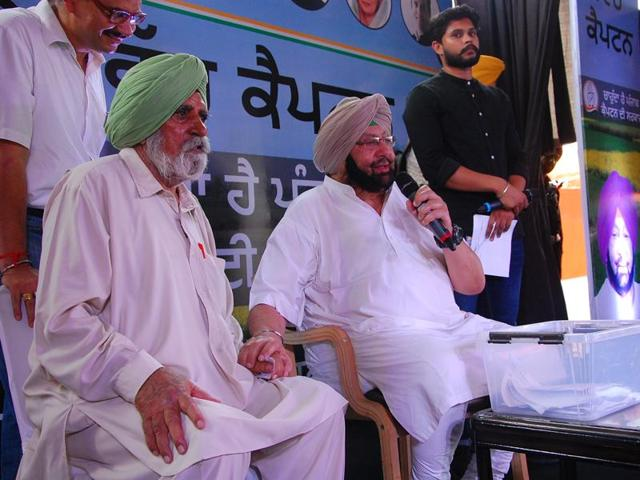 Punjab Congress president Captain Amarinder Singh with Captain Kikkar Singh (retd), his former army colleague from the 1962 war with China, during a programme at Budhlada in Mansa district.