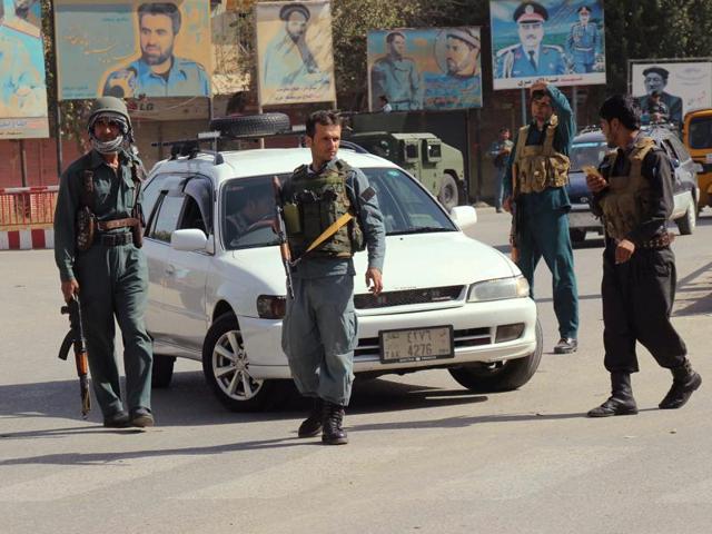 Afghan policemen keep watch in the downtown of Kunduz city, Afghanistan.