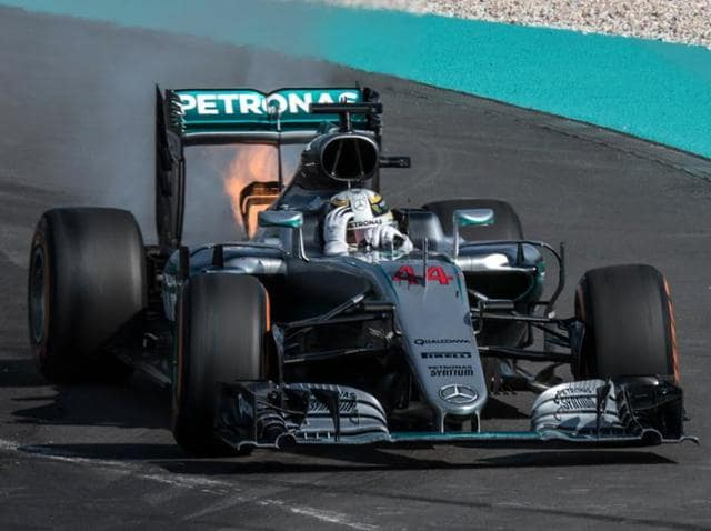 Mercedes AMG Petronas F1 Team's British driver Lewis Hamilton reacts as his car is engulfed in flames.