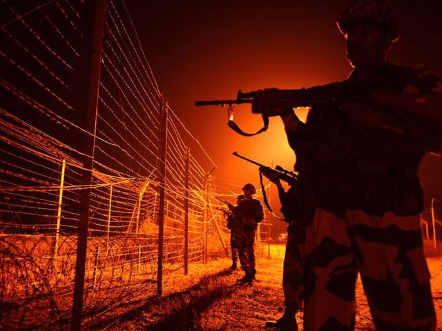 BSF soldiers patrol along a border fence at an outpost along the Line of Control at Abdulian, some 38 kms southwest of Jammu.