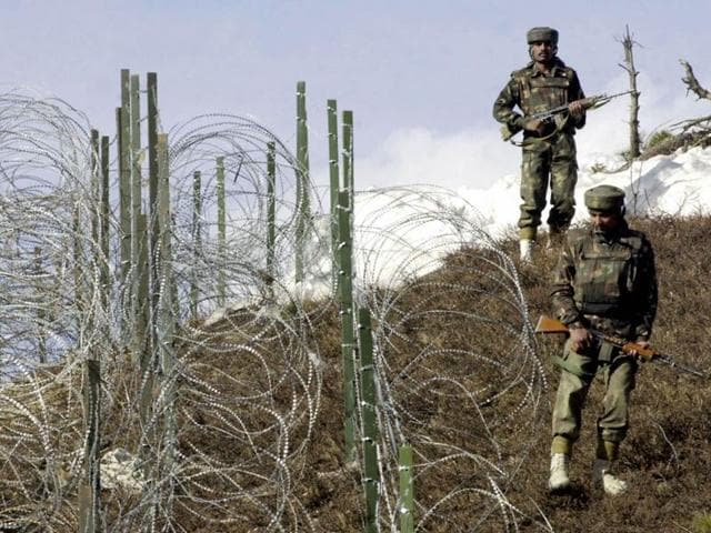Indian soldiers patrol along a barbed-wire fence near Baras Post on the Line of Control between Pakistan and India some 174km north west of Srinagar.