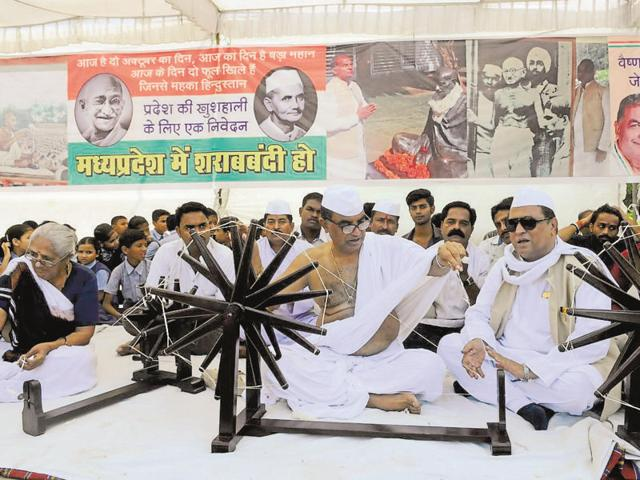 Congress leader Govind Goyal uses a charkha to pay tribute to Mahatma Gandhi, in Bhopal on Sunday.