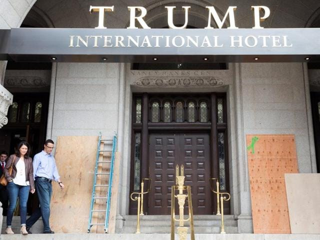 Guests walk past plywood covering graffiti at an entrance to the Trump International Hotel in Washington, US.