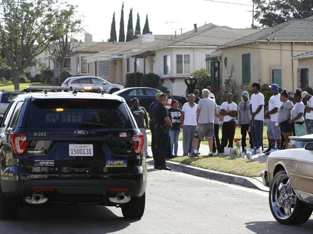 Los Angeles Police officers stop their patrol vehicle to speak to neighbours and members of the community gathered around a makeshift memorial outside a residence on Sunday. Officers shot and killed Carnell Snell Jr. in south Los Angeles on Saturday at the end of a car chase.