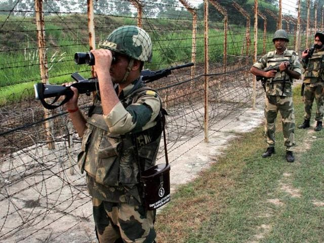 BSF personnel patrol along the India-Pakistan international border at RS Pura near Jammu on Saturday.