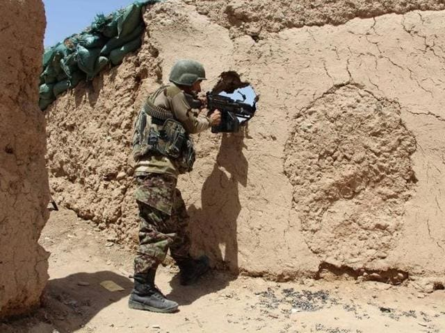 An Afghan National Army (ANA) soldier mans his position at an outpost in Babaji area of Lashkar Gah Helmand province, Afghanistan.