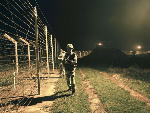 Border Security Force (BSF) soldiers standing guard during a night patrol near the fence at the India-Pakistan International Border at the outpost of Akhnoor sector, about 40 km from Jammu, on Sunday, October 02, 2016.
