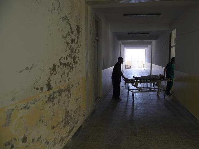 An Afghan patient is wheeled on a trolley past a soaking wall at Salang hospital, north of Kabul.