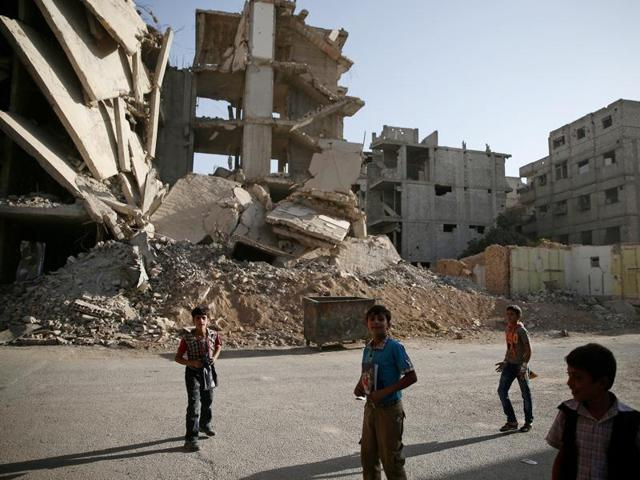 Boys walk near damaged buildings in the rebel-held besieged town of Zamalka, in the Damascus suburbs.