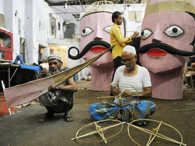 Muslim artisan Vyasudin Khan (white cap), his son Shamu Khan (standing) and a helper working on effigies in SAS Nagar on Monday.
