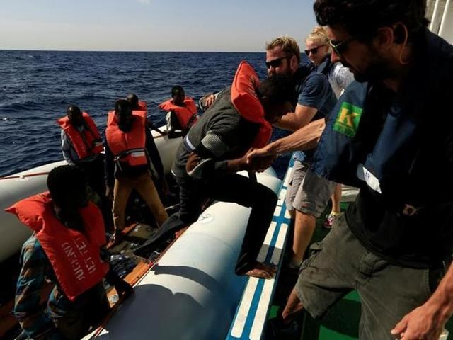 A migrant is transferred from a dinghy by a journalist and members of the German NGO Jugend Rettet during a rescue operation, off the Libyan coast in the Mediterranean Sea.