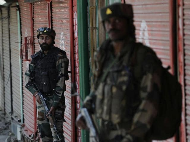 Army soldiers stand guard near a paramilitary camp which was attacked by militants in Baramulla.