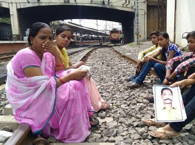 The family of Deshraj Sen sit on rail tracks to demand probe into Sen's disappearance, in Indore on Tuesday morning.