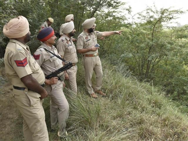 Punjab police officers inspect the area near Rear Kakkar post in Amritsar sector after a Pakistani boat (inset) was seized by the BSF from the Indian waters of the Ravi river on Tuesday.