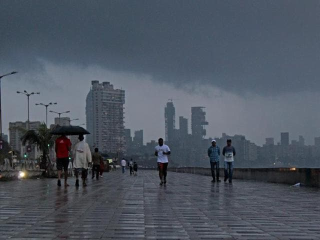 Evening walkers at the Worli seaface brave the rain on Tuesday.