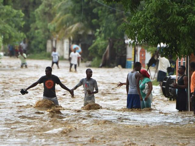 People try to cross the overflowing Rouyonne river in the commune of Leogane, south of Port-au-Prince.