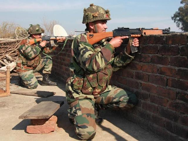 Border Security Force (BSF) soldiers stand guard at an outpost along a fence at the India-Pakistan border in RS Pora south-west of Jammu on October 2, 2016.