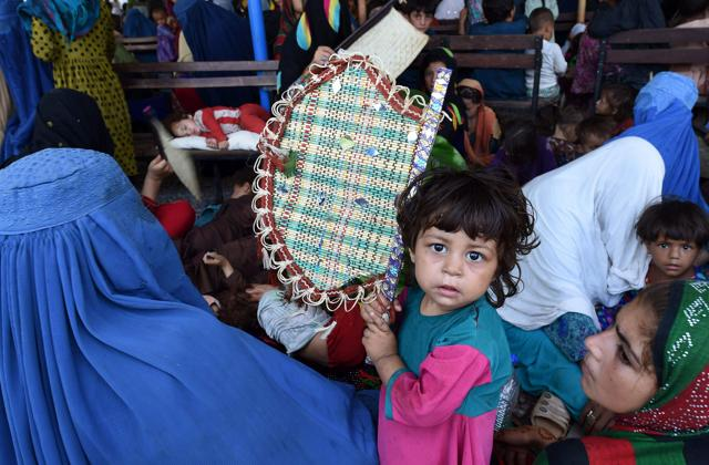 Afghan refugees wait to register at the United Nations High Commissioner for Refugees (UNHCR) repatriation centre on the outskirts of Peshawar, Pakistan.