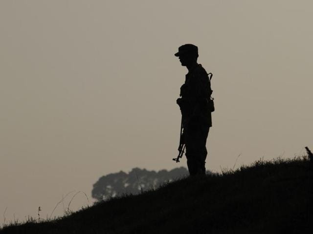 A Pakistan army soldier stands guard at hilltop post at a forward area on the LOC, in Tatta Pani, some 199 kilometers from Islamabad, Pakistan.