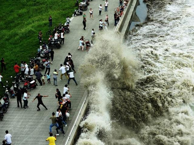 Tidal waves which surged past a barrier on the banks of Qiantang River in Hangzhou, crash onto a street in Zhejiang province, China, on October 4, 2016.