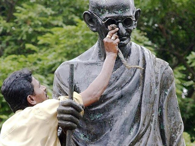 This file photo from October , 2002 shows a civic worker cleaning a statue of Mahatma Gandhi in Bangalore, on the eve of his birth anniversary . Authorities in Ghana authorities announced their intention to
