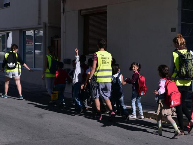 Refugee children are escorted by volunteers for their class at the Refugee Education Chios centre on the Greek island of Chios.
