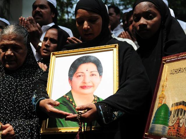People hold a portrait of Tamil Nadu chief minister J Jayalalitha as they pray for her wellbeing front of a hospital where she is being treated in Chennai.