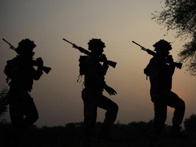 Indian Border Security Force soldiers take up positions at an outpost along a fence at the India-Pakistan border in R.S Pora south-west of Jammu on October 2.