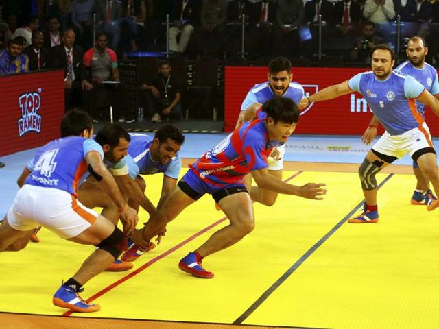 Indian players try to catch South Korean player Tae Beom Kim during their inaugural match.
